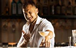 Προκλητικό ασιατικό bartender προετοίμασε ένα κοκτέιλ για το φιλοξενούμενο που χαμογελά στοκ εικόνες