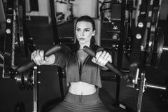 Προκλητικό κορίτσι που κάνει τις ασκήσεις στους θωρακικούς μυς της στον προσομοιωτή στοκ εικόνες