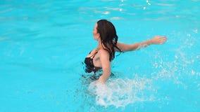 Προκλητικό κορίτσι σε ένα μαύρο κοστούμι λουσίματος που κολυμπά στη λίμνη φιλμ μικρού μήκους