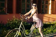 Προκλητικό νέο κορίτσι σε ένα ποδήλατο με τα γυαλιά και το ρόδινο φόρεμα που θέτουν τη συνεδρίαση πορτρέτου στο κάθισμα στοκ φωτογραφία