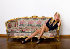 Προκλητικό ξανθό ξάπλωμα στον καναπέ στοκ εικόνες