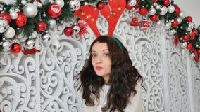 Προκλητικό brunette σε ένα κοστούμι ελαφιών Κέρατα ελαφιών καρναβαλιού, Χριστούγεννα καρναβάλι, αστείο Χριστουγέννων απόθεμα βίντεο
