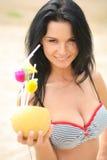 Προκλητικό brunette στην παραλία με ένα κοκτέιλ Στοκ Φωτογραφία