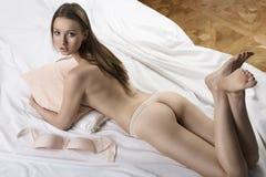 Προκλητικό nude κορίτσι που βρίσκεται στο άσπρο σπορείο με το μαξιλάρι Στοκ εικόνες με δικαίωμα ελεύθερης χρήσης