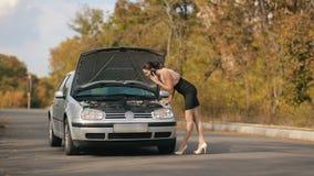 Προκλητικό womam με το σπασμένο αυτοκίνητο στο δρόμο φιλμ μικρού μήκους
