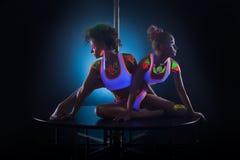 Προκλητικά λεπτά κορίτσια που θέτουν με τα UV σχέδια στο σώμα Στοκ Φωτογραφία