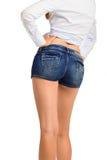Προκλητικά πόδια γυναικών στα σορτς Jean, που απομονώνονται στην άσπρη ανασκόπηση Στοκ Εικόνα
