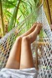 Προκλητικά πόδια γυναικών στην αιώρα όμορφες νεολαίες γυναικών διακοπών λιμνών έννοιας Στοκ Εικόνα