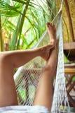 Προκλητικά πόδια γυναικών στην αιώρα όμορφες νεολαίες γυναικών διακοπών λιμνών έννοιας Στοκ Εικόνες