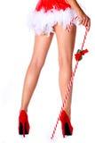Προκλητικά πόδια. Κορίτσι Santa με το τεράστιο ραβδί καλάμων καραμελών που απομονώνεται Στοκ Εικόνες