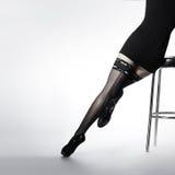 Προκλητικά πόδια μιας νέας γυναίκας στις μαύρες γυναικείες κάλτσες Στοκ Φωτογραφίες