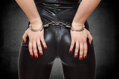 Προκλητικά χέρια dominatrix στο γάιδαρο στις χειροπέδες Στοκ Εικόνα