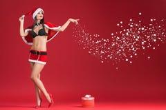 Προκλητικές γυναίκες στα ενδύματα Άγιου Βασίλη με το δώρο Χριστουγέννων Στοκ εικόνα με δικαίωμα ελεύθερης χρήσης