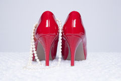 Προκλητικές κόκκινες αντλίες με τα μαργαριτάρια Στοκ Φωτογραφίες