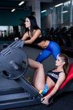 Προκλητικές φίλαθλες γυναίκες που κάνουν την άσκηση ικανότητας δύναμης στην αθλητική γυμναστική Όμορφα κορίτσια που επιλύουν στη  στοκ φωτογραφίες