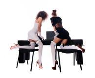 Προκλητικές δύο γυναίκες στο γραφείο με ένα lap-top Στοκ Φωτογραφίες