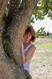 Προκλητική γηράσκουσα γυναίκα πίσω από ένα δέντρο για την προστασία ομορφιάς Στοκ Φωτογραφίες