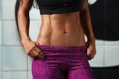 Προκλητική γυναίκα ικανότητας που παρουσιάζει τα ABS και επίπεδη κοιλιά Όμορφο μυϊκό κορίτσι, διαμορφωμένη κοιλιακή, λεπτή μέση Στοκ Φωτογραφίες