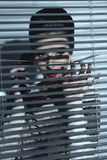 Προκλητική γυναίκα κατασκόπων πίσω από τα παραθυρόφυλλα στοκ εικόνες