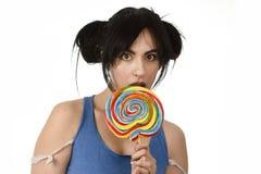 Προκλητική γυναίκα με τα ponytails που δαγκώνουν τα χείλια της που γλείφουν το γλυκό μεγάλο lollipop καραμέλας Στοκ Εικόνες