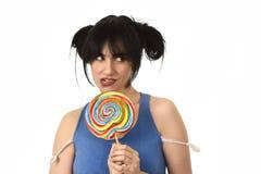 Προκλητική γυναίκα με τα ponytails που δαγκώνουν τα χείλια της που κρατούν και που γλείφουν το γλυκό μεγάλο lollipop καραμέλας Στοκ Εικόνα