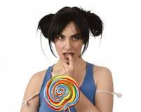 Προκλητική γυναίκα με τα ponytails που δαγκώνουν τα χείλια της που κρατούν και που γλείφουν το γλυκό μεγάλο lollipop καραμέλας Στοκ φωτογραφίες με δικαίωμα ελεύθερης χρήσης
