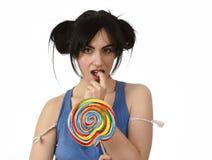 Προκλητική γυναίκα με τα ponytails που δαγκώνουν τα χείλια της που κρατούν και που γλείφουν το γλυκό μεγάλο lollipop καραμέλας Στοκ φωτογραφία με δικαίωμα ελεύθερης χρήσης