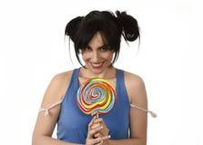 Προκλητική γυναίκα με τα ponytails που δαγκώνουν τα χείλια της που κρατούν και που γλείφουν το γλυκό μεγάλο lollipop καραμέλας Στοκ Εικόνες