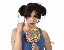 Προκλητική γυναίκα με τα ponytails που δαγκώνουν τα χείλια της που κρατούν και που γλείφουν το γλυκό μεγάλο lollipop καραμέλας Στοκ Φωτογραφία