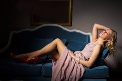Προκλητική γυναίκα που βάζει στο φανταχτερό καναπέ Στοκ Φωτογραφία