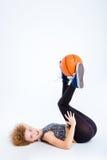 Προκλητική γυναίκα που βρίσκεται στο πάτωμα με τη σφαίρα καλαθοσφαίρισης Στοκ Εικόνες