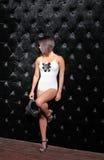 Προκλητική γυναίκα στην άσπρη στάση σωμάτων κοντά στο μαύρο τοίχο με το καπέλο Στοκ Φωτογραφίες