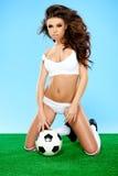 Προκλητική γυναίκα στην τοποθέτηση εσώρουχων με τη σφαίρα ποδοσφαίρου Στοκ Φωτογραφία