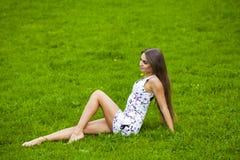 Προκλητική γυναίκα στη σύντομη συνεδρίαση φορεμάτων στην πράσινη χλόη Στοκ Εικόνες