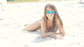 Προκλητική γυναίκα στη swimwear και χύνοντας άμμο στην παραλία αργά απόθεμα βίντεο