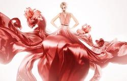 Προκλητική γυναίκα στο κόκκινο φόρεμα με τα λουλούδια Στοκ Φωτογραφία