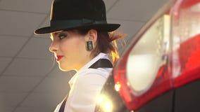 Προκλητική γυναίκα στο μαύρο καπέλο που εξετάζει τη κάμερα και φιλμ μικρού μήκους