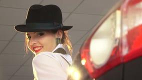 Προκλητική γυναίκα στο μαύρο καπέλο που εξετάζει τη κάμερα φιλμ μικρού μήκους