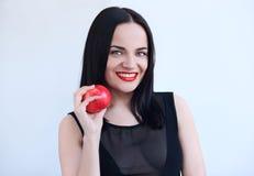 Προκλητική γυναίκα στο Μαύρο με το κόκκινο μήλο Στοκ εικόνα με δικαίωμα ελεύθερης χρήσης