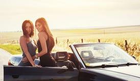 Προκλητική γυναίκα brunette δύο που στέκεται κοντά στο αυτοκίνητό της Στοκ Φωτογραφία