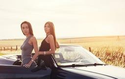 Προκλητική γυναίκα brunette δύο που στέκεται κοντά στο αυτοκίνητό της Στοκ Εικόνες