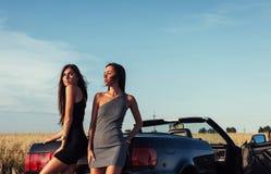 Προκλητική γυναίκα brunette δύο που στέκεται κοντά στο αυτοκίνητό της Στοκ Εικόνα