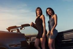 Προκλητική γυναίκα brunette δύο που στέκεται κοντά στο αυτοκίνητό της Στοκ φωτογραφία με δικαίωμα ελεύθερης χρήσης