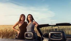 Προκλητική γυναίκα brunette δύο που στέκεται κοντά στο αυτοκίνητό της Στοκ φωτογραφίες με δικαίωμα ελεύθερης χρήσης