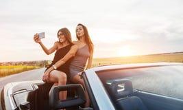 Προκλητική γυναίκα brunette δύο που στέκεται κοντά στο καμπριολέ Στοκ φωτογραφία με δικαίωμα ελεύθερης χρήσης