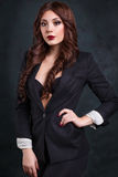 Προκλητική επιχειρησιακή γυναίκα σε ένα σκοτεινό επιχειρησιακό κοστούμι Όμορφος προκλητικός γραμματέας Στοκ Εικόνες
