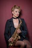 Προκλητική ελκυστική γυναίκα με την τοποθέτηση saxophone στο κόκκινο υπόβαθρο Νέο αισθησιακό ξανθό σκεπάρνι παιχνιδιού Μουσικό όρ Στοκ Εικόνα