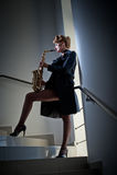 Προκλητική ελκυστική γυναίκα με το saxophone και τα μακριά πόδια που θέτουν στα σκαλοπάτια Νέο ελκυστικό ξανθό σκεπάρνι παιχνιδιο Στοκ Εικόνα
