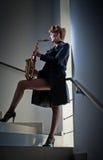 Προκλητική ελκυστική γυναίκα με το saxophone και τα μακριά πόδια που θέτουν στα σκαλοπάτια Νέο ελκυστικό ξανθό σκεπάρνι παιχνιδιο Στοκ Φωτογραφίες