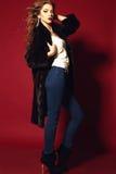 Προκλητική κυρία με το ξανθό σγουρό jair στο τζιν παντελόνι και το μαύρο παλτό γουνών Στοκ φωτογραφίες με δικαίωμα ελεύθερης χρήσης